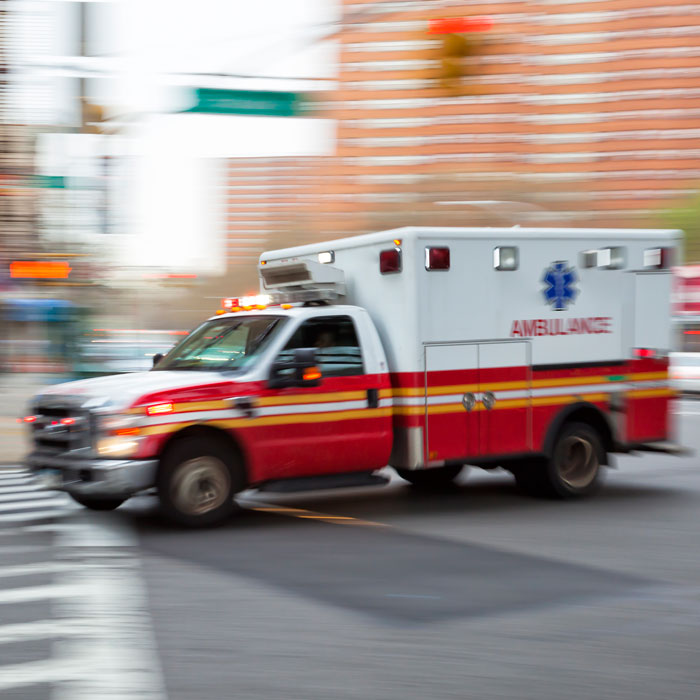 Picture of an ambulance speeding through a downtown street
