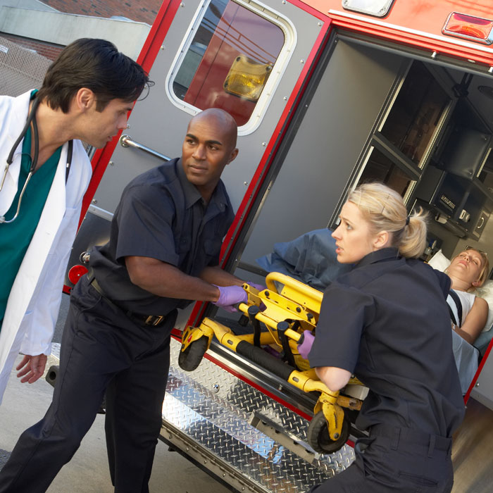 Picture of a doctor and two EMTs responding to an emergency